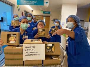 Six nurses in blue scrubs and masks next to a table full of Urth Caffé lunch boxes with Thank You sign.
