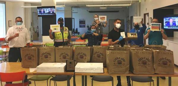 Group of Beverly Hills Public Works employees standing behind long table with many brown Urth bags of lunch boxes. The poeple are holding Thank You cards.