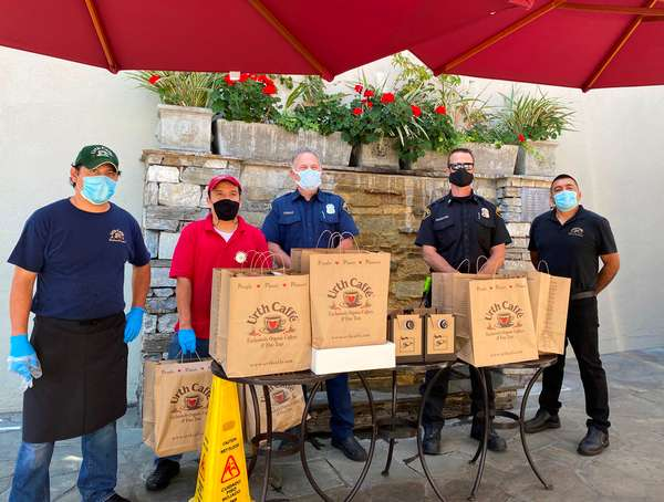 Two Urth employees and three Beverly Hills firemen standing behind table with Urth bags of lunch boxes and coffee. Rock wall fountain with flowers in background.