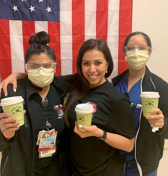 3 nurses holding green Urth Caffé To Go coffee cups. They are standing in front of a vertical USA flag, two with masks and protective eye wear and the one without a mask is smiling.