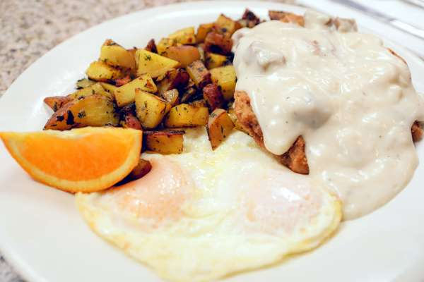 Country fried steak with fried egg and potatoes