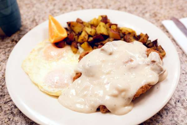 Country fried steak with fried eggs and potatoes