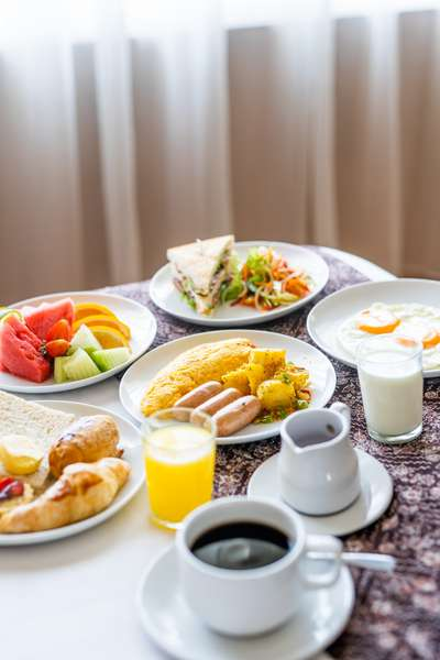 Various plates of fruit, eggs, sausage and other breakfast eats