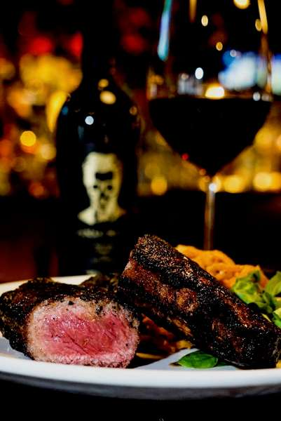 rare steak dish and glass of wine