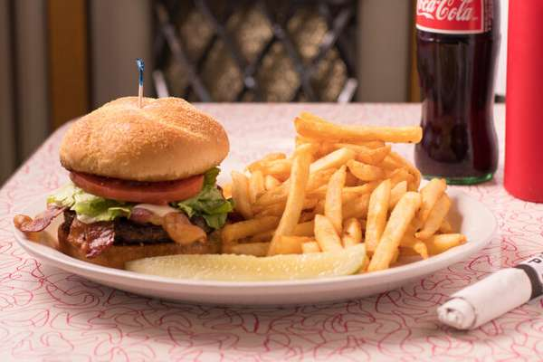 Hamburger with fries, and a Coca-Cola in a glass bottle