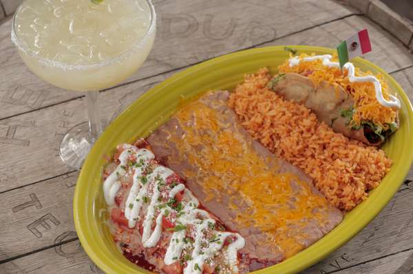 combo number five, an cheese enchilada topped with crema and a tinga taco with a side of rice and beans.
