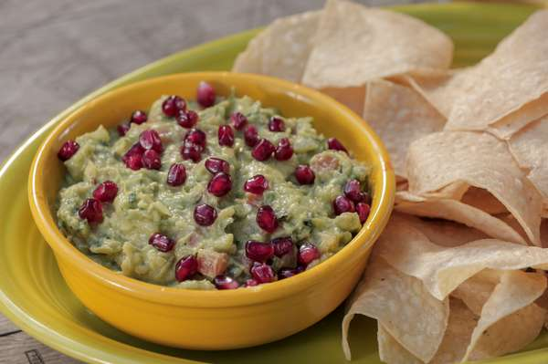 guacamole topped with pomegranate seeds served with homemade chips