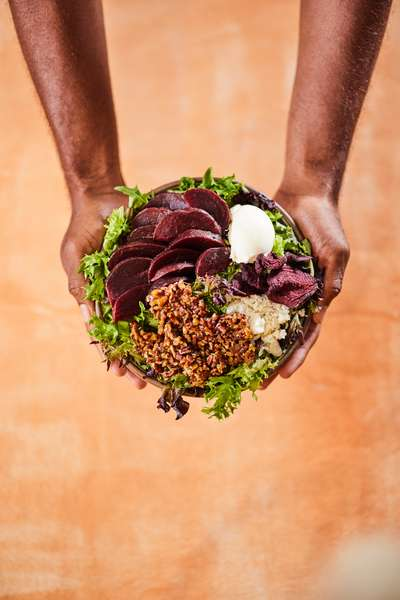 Man holding a bowl of plant based food
