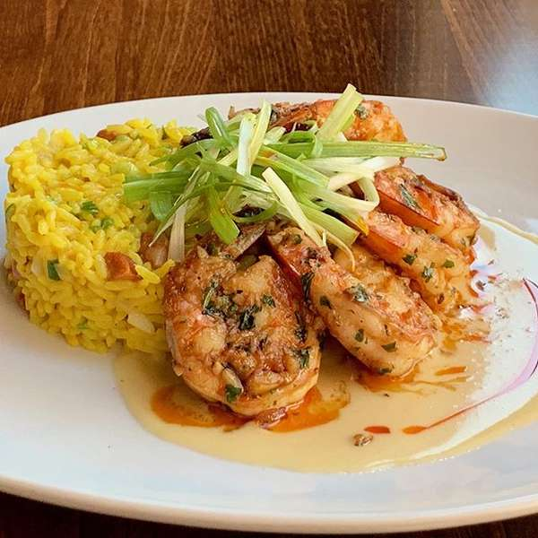 Sautéed jumbo garlic shrimp with chorizo saffron paella rice and red chili oil