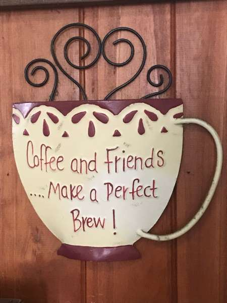 """large sign shaped like a coffee cup and reading """"coffee and friends bake a perfect brew"""""""