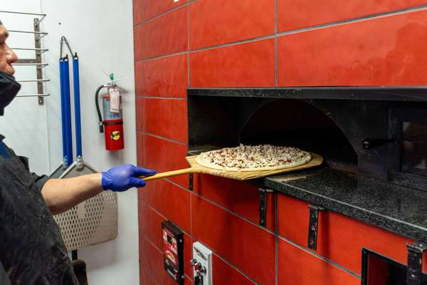 Pulling pizza out of brick oven