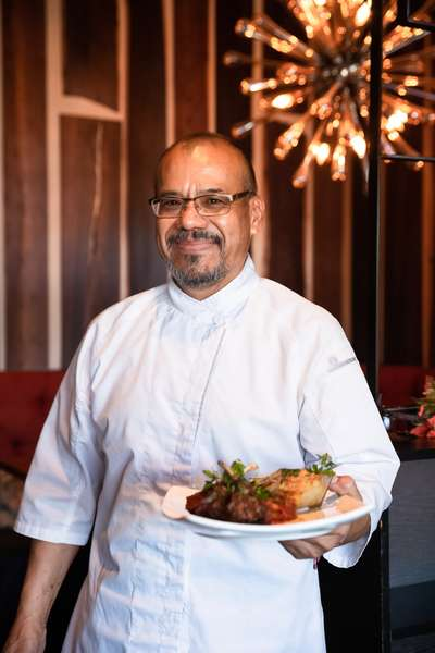 Chef Lucio holding a plate