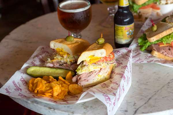 sandwich with pickle, chips and beer