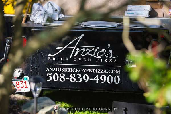 Anzio's Brick Oven Pizza sign on table at wedding