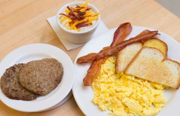 plates with eggs, toast, bacon and sausage