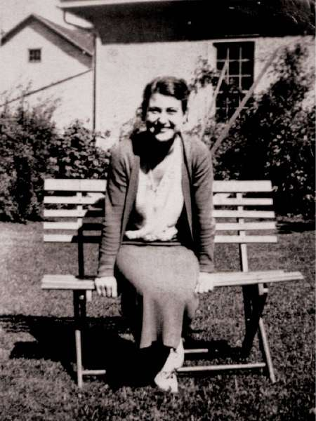old black and white photo of Comella's family member a lady sitting on a bench
