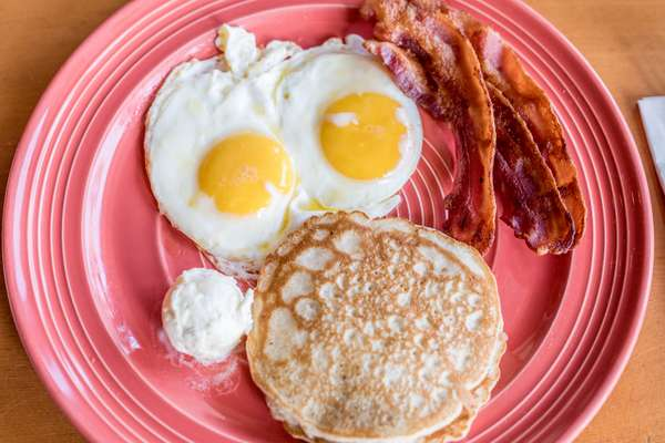 breakfast plate with pancakes, bacon and eggs