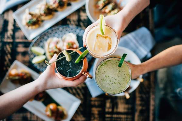 Friends cheering with different cocktails