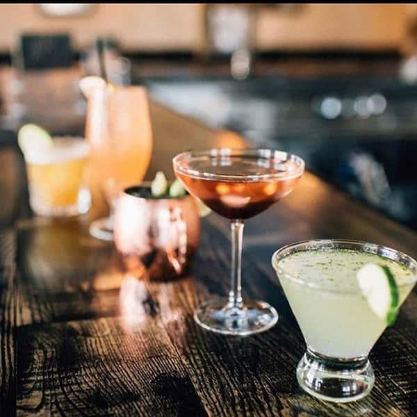 Different drinks sitting on a dark wood bar