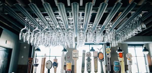 Dozens of wine glasses hanging on a rack