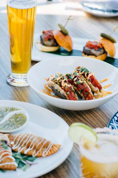 Multiple different menu items plated with a beer