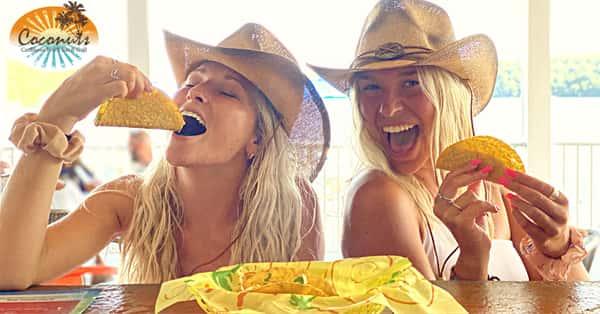 women eating tacos