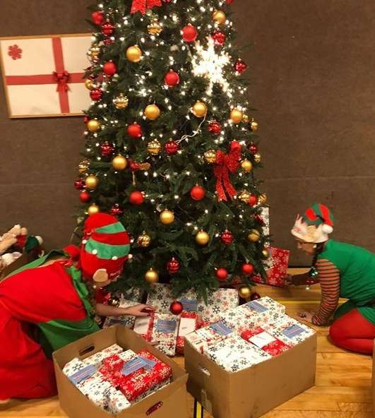 two people placing gifts under a christmas tree