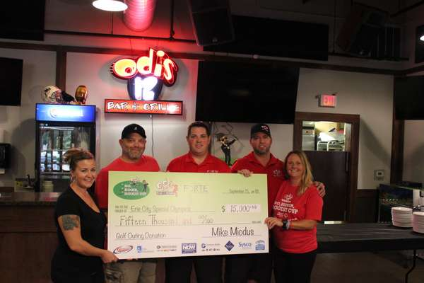 5 people holding a large check