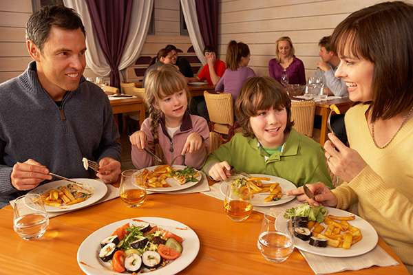 family sitting at table with plates of food