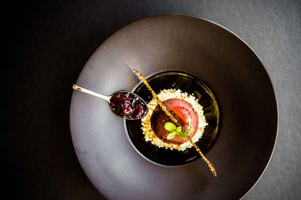 Chocolate Mousse: Delectable chocolate mousse on a bed of crushed cashew nuts served over blue and black berry sauce.