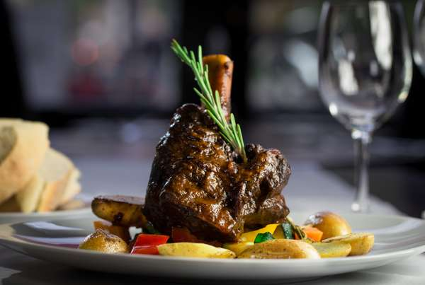 Lamb Shank: Slow braised lamb shank in red wine, garlic and rosemary, served with potatoes and mixed vegetables