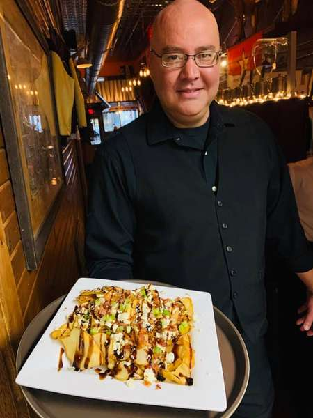 man chef holding loaded fries