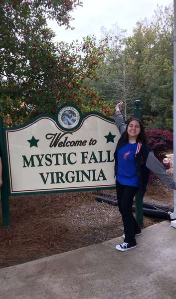 person by Mystic Falls Virginia sign