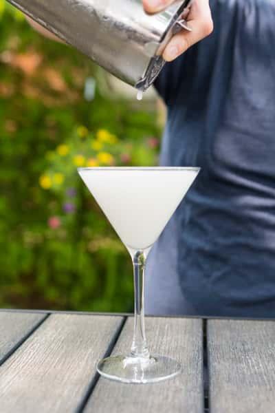 person pouring martini