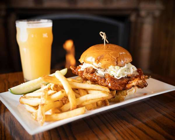 Southwestern chicken sandwich with fries and a glass of beer