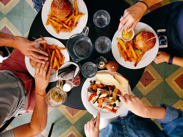 four people dining on burgers