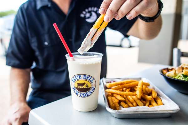 Man dipping moonie's fries into a moonie's shake