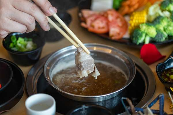 Dipping wagyu beef in broth.