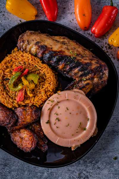 Grilled Beef Ribs with side of fried rice, moi moi and plantains