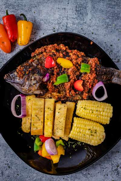Grilled Whole Tilapia with a side of fried yam & corn