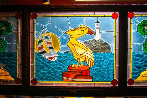 Stained glass of yellow Seagull with a lighthouse in the background