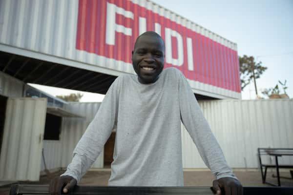 Fudi Logo Behind Man