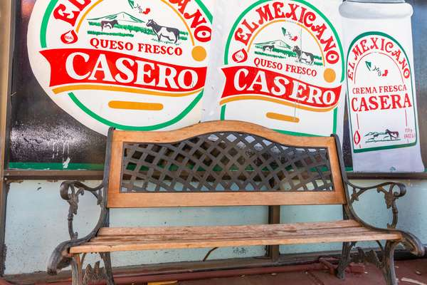 wooden bench under Queso Fresco Casero sign