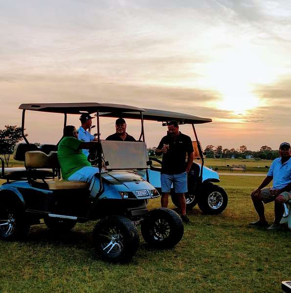 members on golf course at sunset