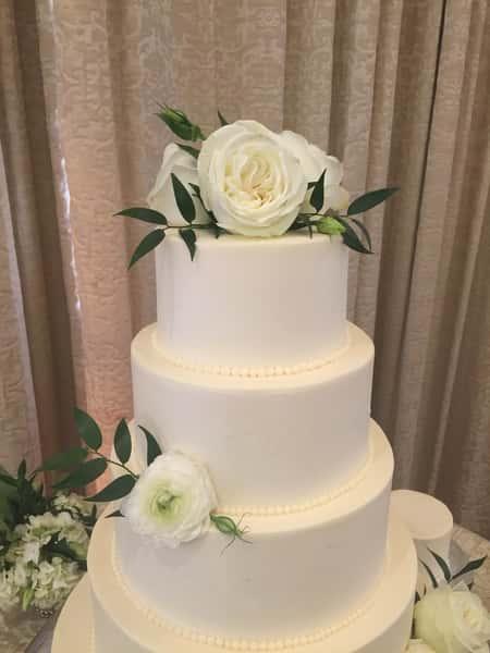 white cake with white roses
