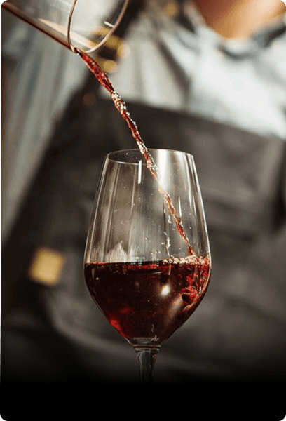 Person pouring red wine into wine glass